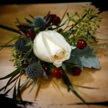 Creme rose boutonniere with agonis, hypericum, eryngium, seeded
